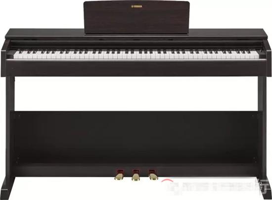 """YDP-103R的整体设计与我们所熟悉的ARIUS系列非常相似,简洁的厢式外观设计,配合经典的深玫瑰木色,使整台琴看起来大气、简约,适合在各种不同的环境中摆放。  谱板上金色的""""Yamaha""""LOGO,彰显了这台琴的贵族血统,在印度尼西亚的工厂""""出生"""",漂洋过海来到中国。  当下最流行的极简设计风格融入到这台琴的面板设计,摒弃复杂,使用基本元素,简单的功能交互,能承载整个产品的功能操作。  琴盖边条的设计由原来ARIUS系列的银色金属质感边条变为更加具有质感"""